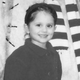 Portret alb negru al Arianei Grande în copilărie în timp ce poartă o bluză neagră