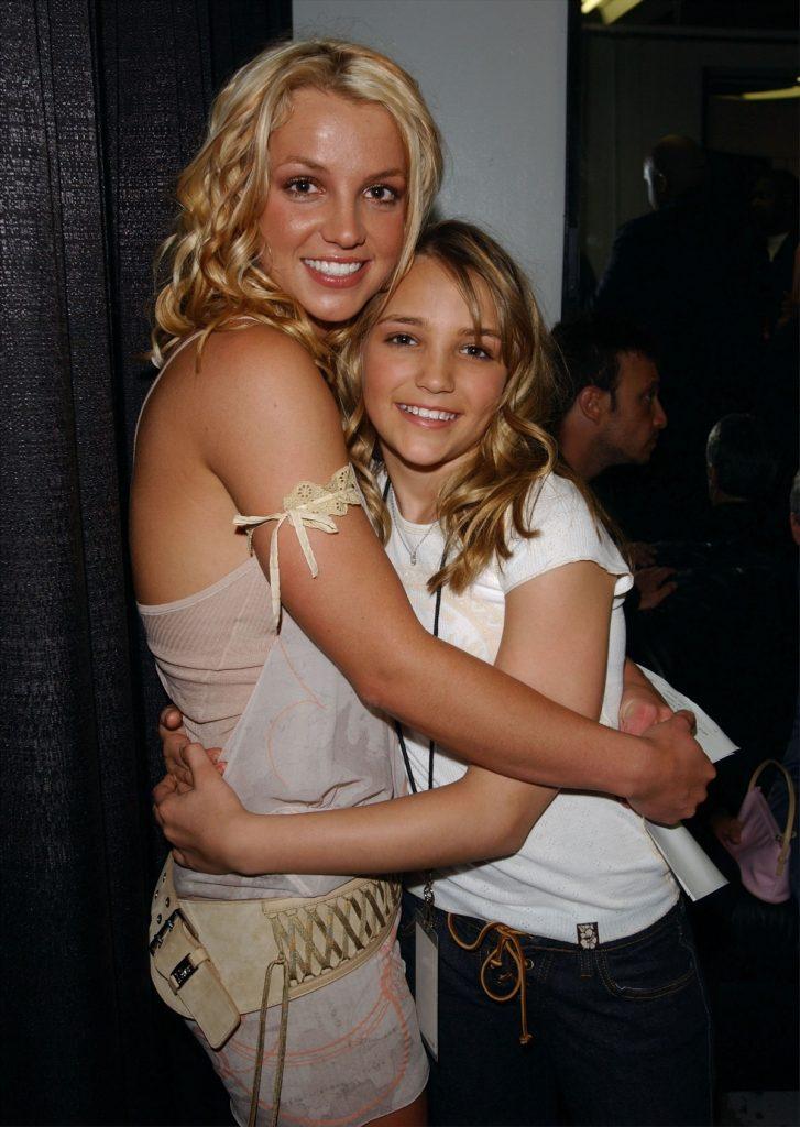Britney Spears într-o rochie cu paiete în timp ce o ține în brațe pe sora sa Jamie Lynn Spears îmbrăcată într-un tricou alb în timp ce iau parte la gala anuala de la Kids' Choice Awards din anul 2003