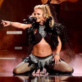 Cântăreața Britney Spears în timp ce stă în genunchi într-un costum negru pe scenă și arată cu mâna către public