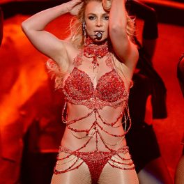 Britney Spears într-un costum de scenă roșu în timp ce își ține mâinile în păr în timpul concertului