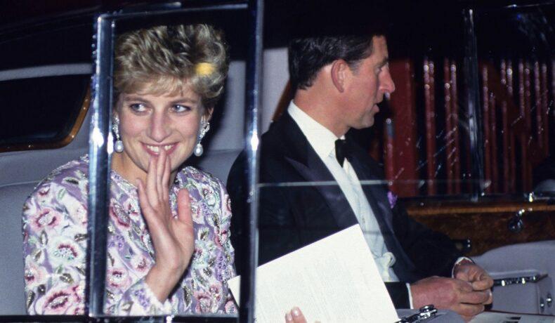 Prințesa Diana alături de Prințul Charles într-o mașină în timp ce face cu mâna publicului la Gala de la Earls Court din 26 octombrie 1992