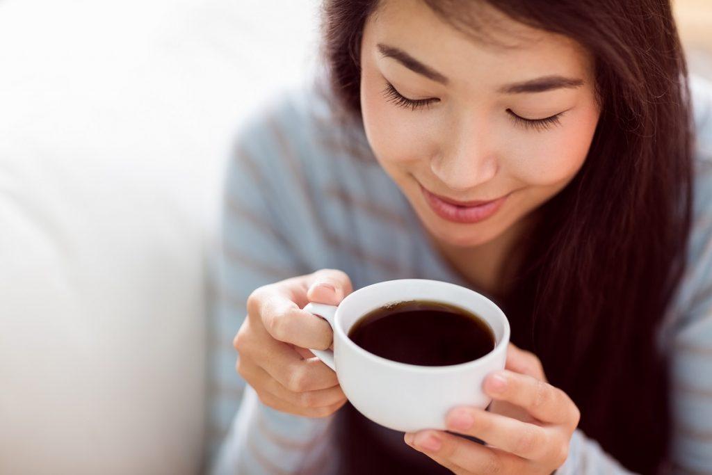 O tânără care ține în mână o cească albă de cafea după ce a aflat când e recomandat să bei cafea