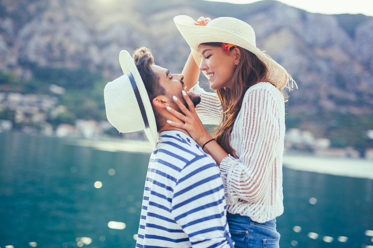 Un cuplu care se ține în brațe în timp ce se sărută și poartă pălării de soare