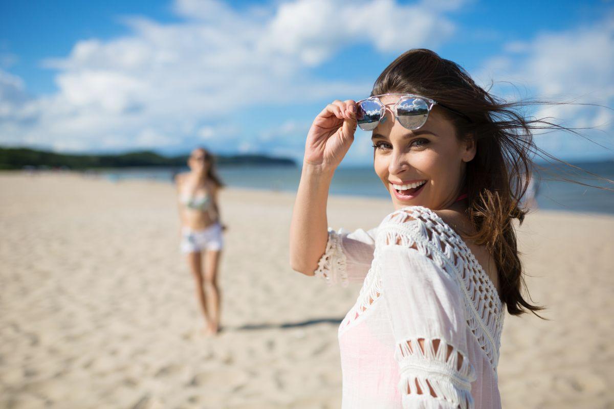 O femeie frumoasă, îmbrăcată în alb, își ridică ochelarii de soare, în timp ce se află pe plajă