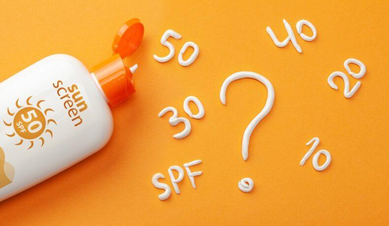 o masă portocalie pe care se află o cremă de protecție solară pentru a explica ce este SPF-ul și la ce te ajută folosirea sa
