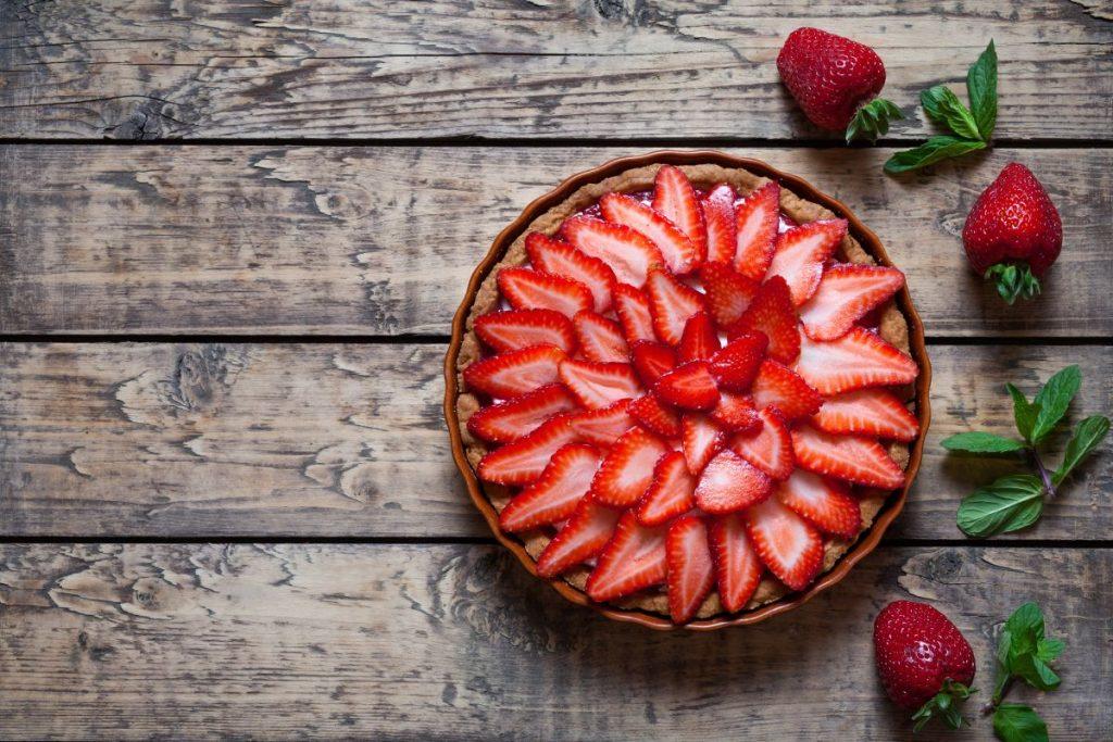 O tartă cu căpșuni, pe masă de lemn