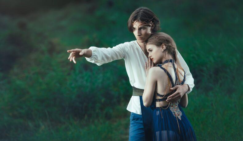 O pajiște pe care se află unul dintre cei mai atrăgători bărbați ai zodiacului îmbrăcat într-o cămașă albă în timp ce își ține la piept iubita frumoasă care poartă o rochie albastră și privește către tărâmurile pe care i le arată iubitul său