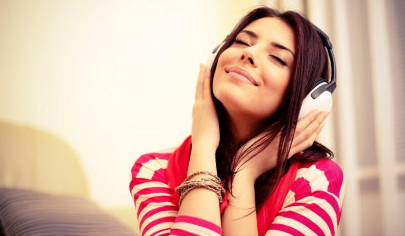 O tânără surânde, cu ochii închiși, în timp ce ascultă muzică la cășți