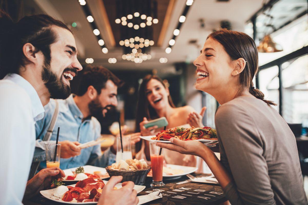 Grup de prieteni, fericiți, care iau masa împreună