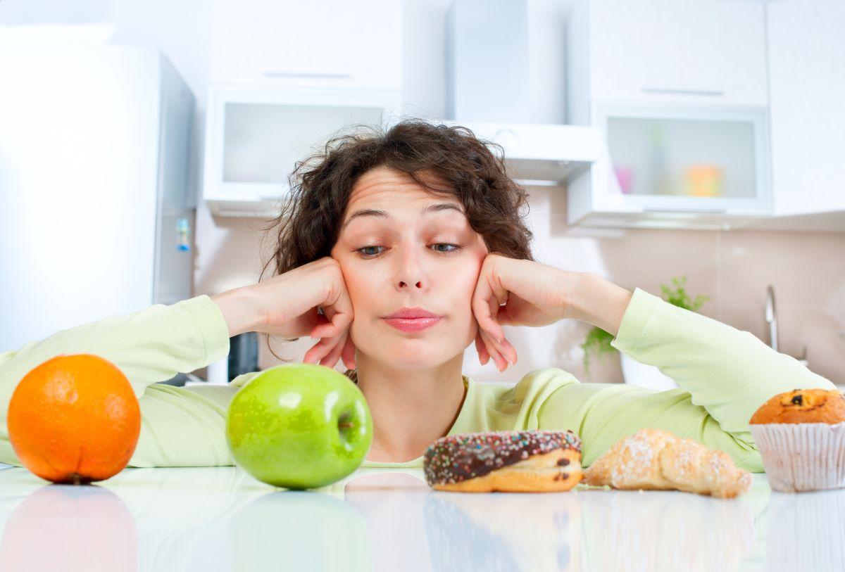 O femeie care trebuie să facă alegerea între mâncare sănătoasă și nesănătoasă
