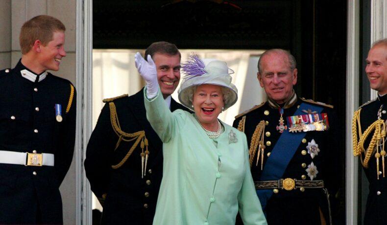Regina Elisabeta îmbrăcată în costum verde în timp ce face cu mâna publicului de la balcon alături de Prințul Philip și alte figuri din corpul Regal la ceremonia oficială a comemorării zilei naționale în iulie 2005