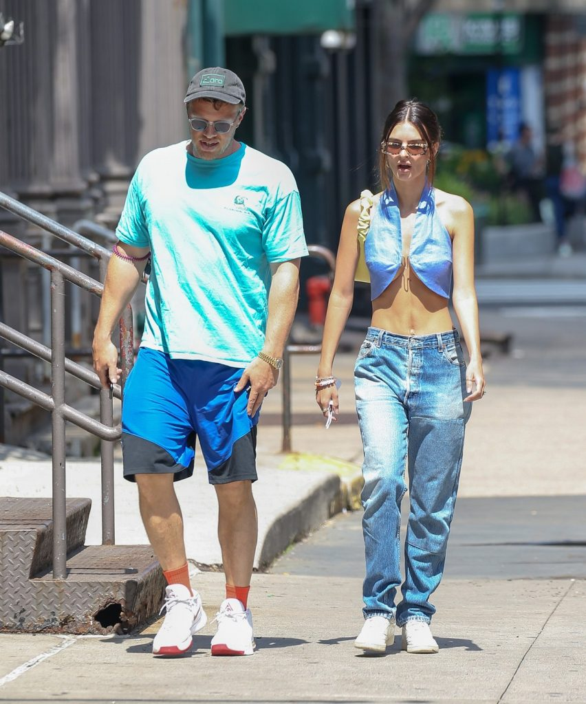 Emily Ratajkowski într-o bluză albastră care îi lasă abdomenul la vedere și o pereche de blugi lungi alături de soțul ei Sebastian Bear-McClard ]n timp ce se plimb[ pe străzile din New York