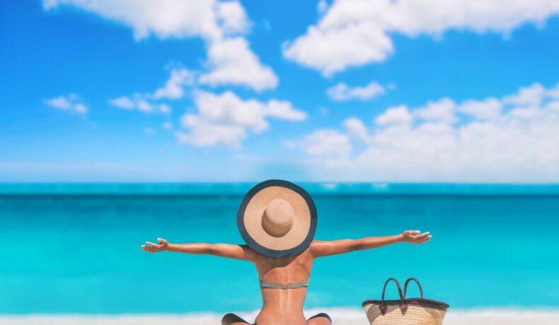 O femeie stă pe plajă, cu fața spre mare și spatele spre camera. Are o pălărie mare de paie și își întinde brațele