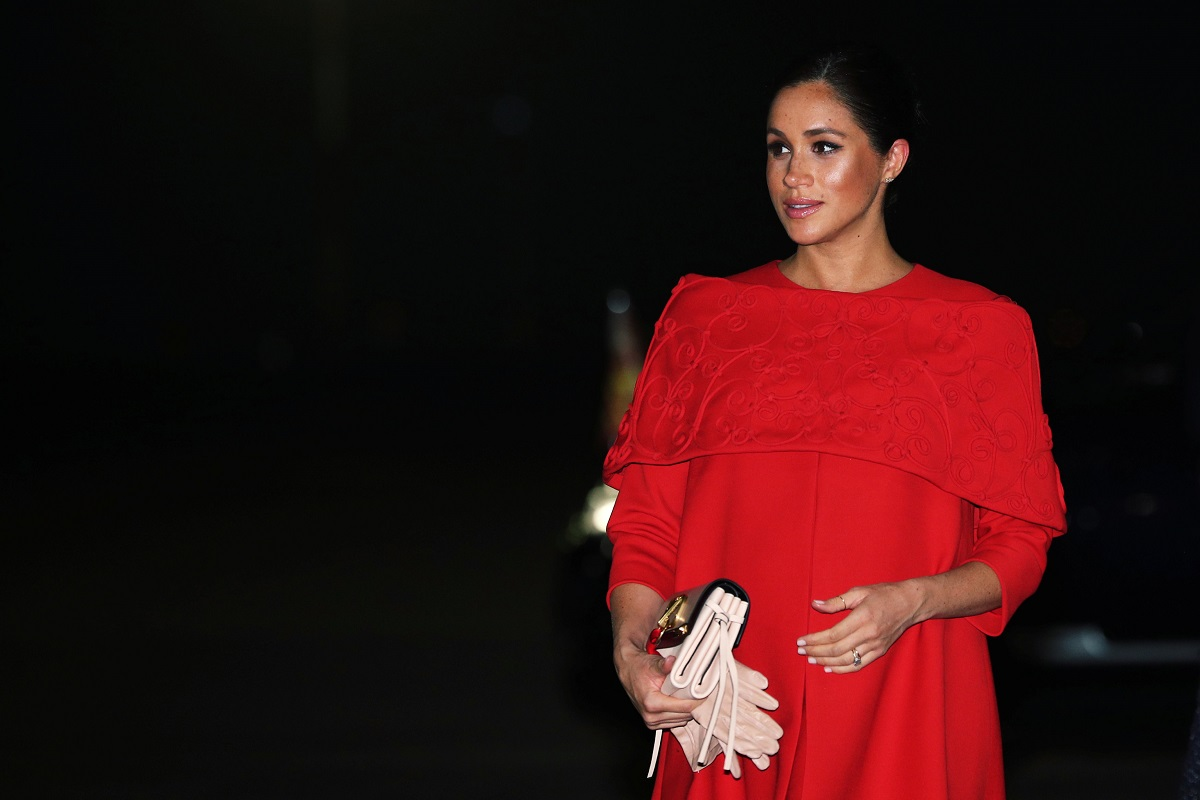 Meghan Markle într-o rochie roșie în timp ce ăși ține mâna pe burtică este una dintre cele trei femei din Familia Regală a Marii Britanii care au devenit mame după vârsta de 30 de ani