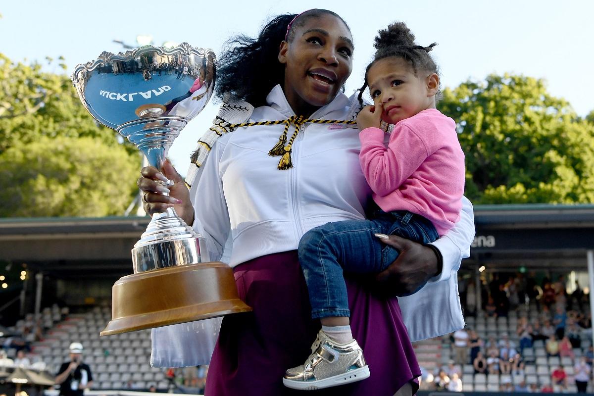 Fiica Serenei Williams, Olympia într-un hanorac roz în timp ce stă în brațele mamei sale care ține în cealaltă mână un torfeu pe care l-a obținut împotriva sportivei Jessica Pegula