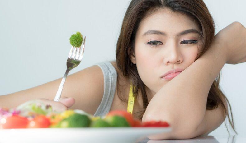 O femeie care ține cotul pe masă în timp ce privește o farfurie cu legume și este indecisă dacă să le consume deaorece imaginea sa de sine este scăzută și suferă de o tulburare de alimentație
