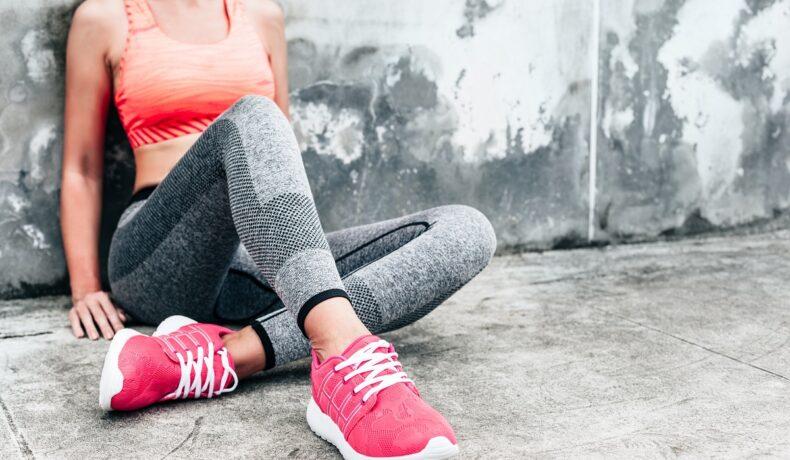 O tânără îmbrăcată într-o ținută sport în timp ce poartă încălțăminte sport roz