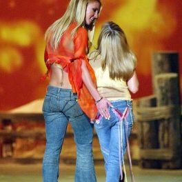 Britney Spears cu spatele în timp ce o ține după umăr pe sora sa Jamie Lynn Spears pe scenă la The Teen Choice Awards din 2002