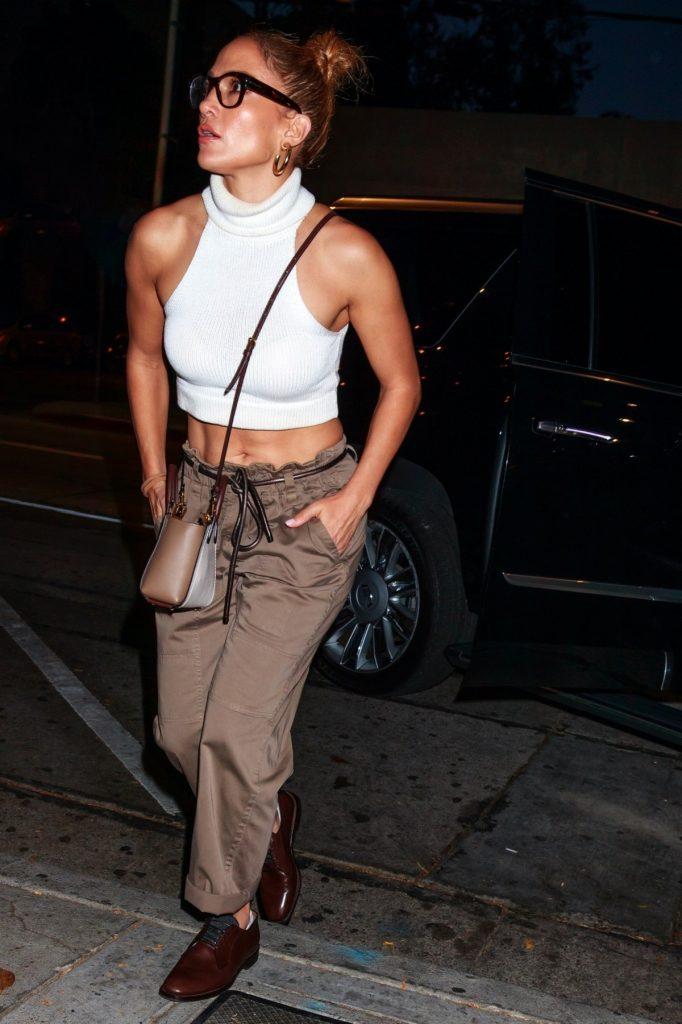 Jennifer Lopez purtând o bluză albă pe gât fără mâneci și o pereche de pantaloni timp cargo maro, la care a accesorizat o borsetă și o pereche de ochelari negri, în timp ce merge să ia cina alături de Lynda Lopez