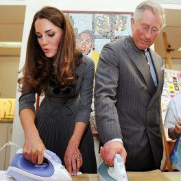 Prințul Charles la costum alături de Kate Middleton în rochie gri în timp ce amândoi țin în mână un fier de călcat în timpul vizitei de la galeria de artă Dulwich din 2012