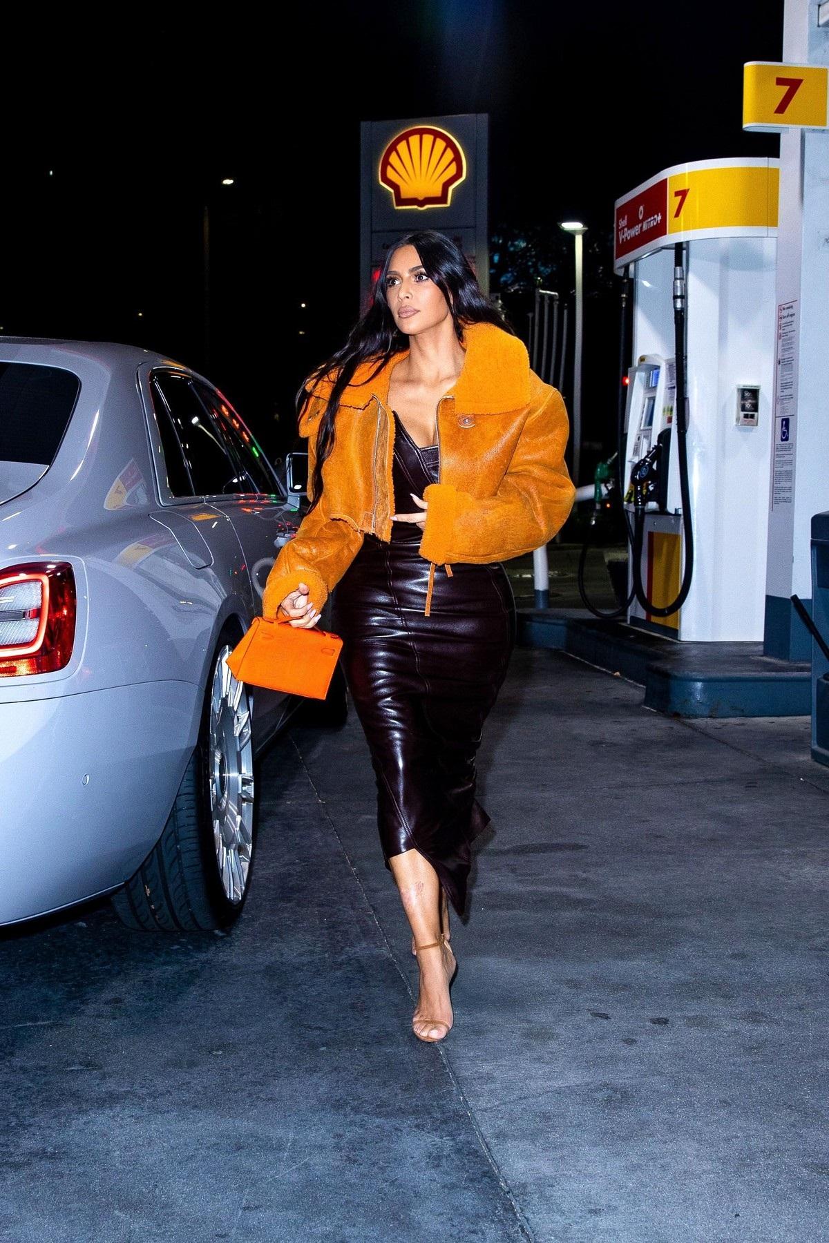 Kim Kardashian a purtat o jachetă orange de la un brand deținut de Kanye West la care a asortat o rochie din piele neagră și o pereche de tocuri nude în timp ce a făcut cumpărături într-o parcare din Los Angeles