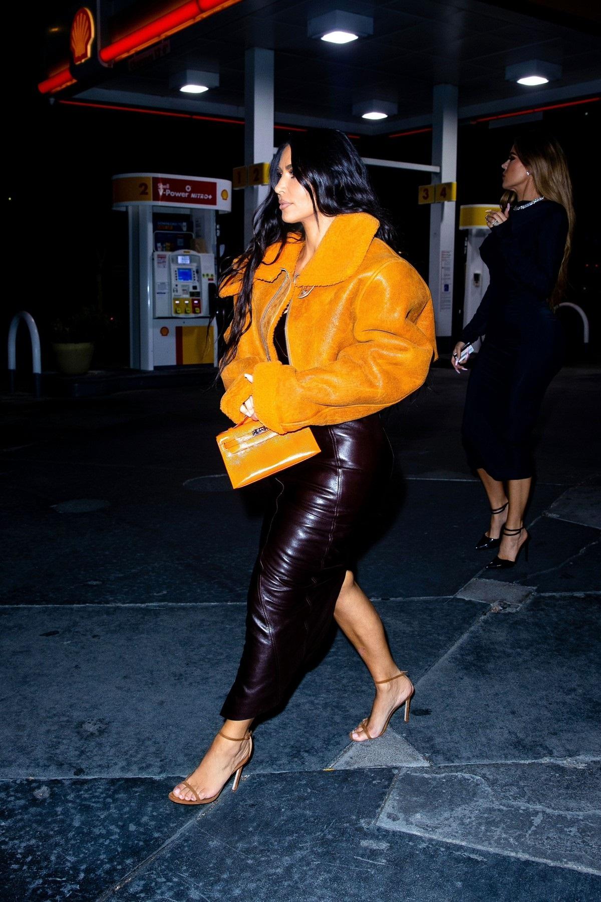 Kim Kardashian mergând la cumpărături într-o parcare din Los Angeles în timp ce poartă o rochie mulată de piele neagră și o jachetă de la un brand deținut de Kanye West