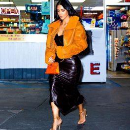 Kim Kardashian purtând o rochie neagră de piele, tocuri nude și o jachetă de la un brand deținut de Kanye West în timp ce se afla în parcare