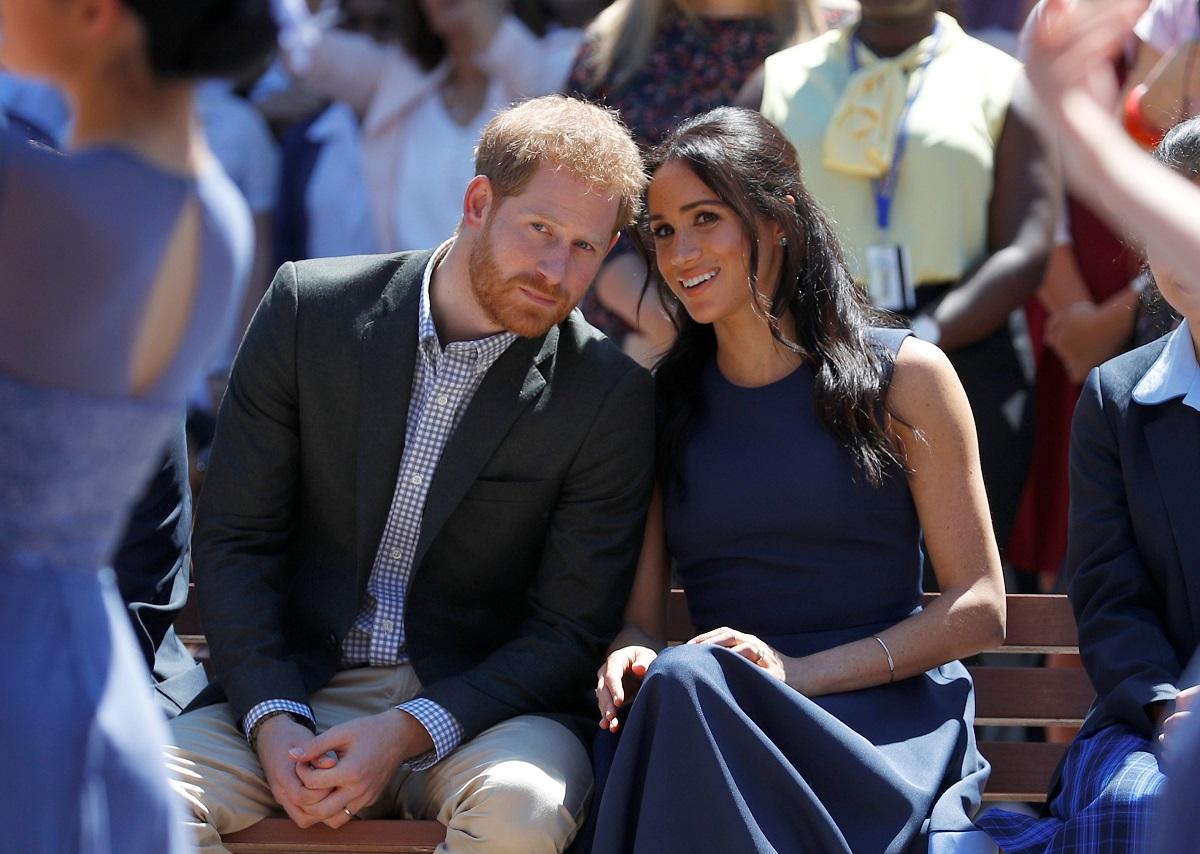 Prințul Haary alături de soția sa Meghan Markle în timp ce stau apropiați unul de celălalt pe scaune și privesc spre camere în Australia în timpul unei vizite la liceul de fete Macarthur
