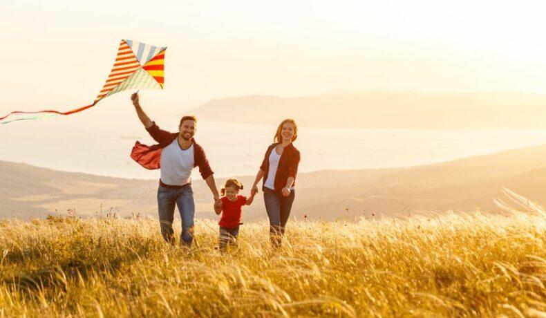 O familie fericită se plimbă pe un câmp, în timp ce tatăl înalță un zmeu