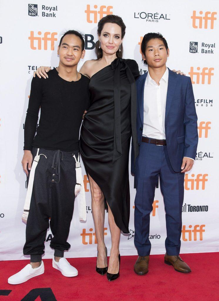 Maddox Jolie Pitt îmbrăcat în costum negru alături de Angelina Jolie în rochie neagră și Pax Jolie Pitt la costum albastru, pe covorul roșu la premiera filmului First They Killed My Father