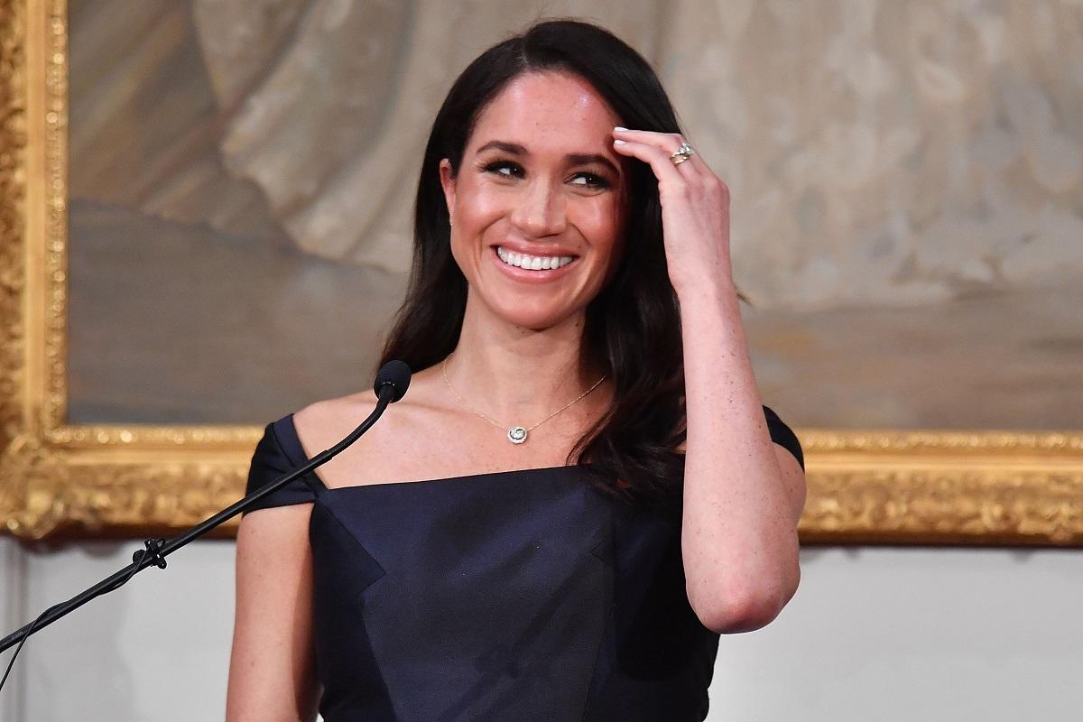 Meghan Markle într-o rochie neagră la un pupitru în timp ce își dă părul după ureche și ține un discurs în Noua Zeelandă în cadrul unei recepții organizate de Guvern