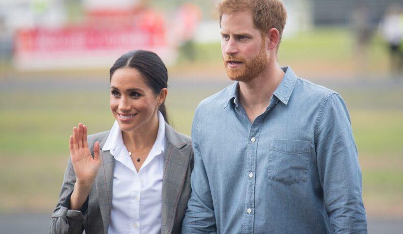 Meghan Markle, care nu va participa la dezvelirea statuii Prințesei Diana, îmbrăcată într-o cămașă albă și un sacou gri în timp ce face cu mâna oamenilor și este alături de soșțul său, Prințul Harry îmbrăcat într-o cămașă de culoare albastră