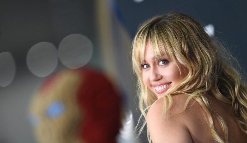 Portret cu artista Miley Cyrus în timp ce zâmbește la premiera filmelor Marvel