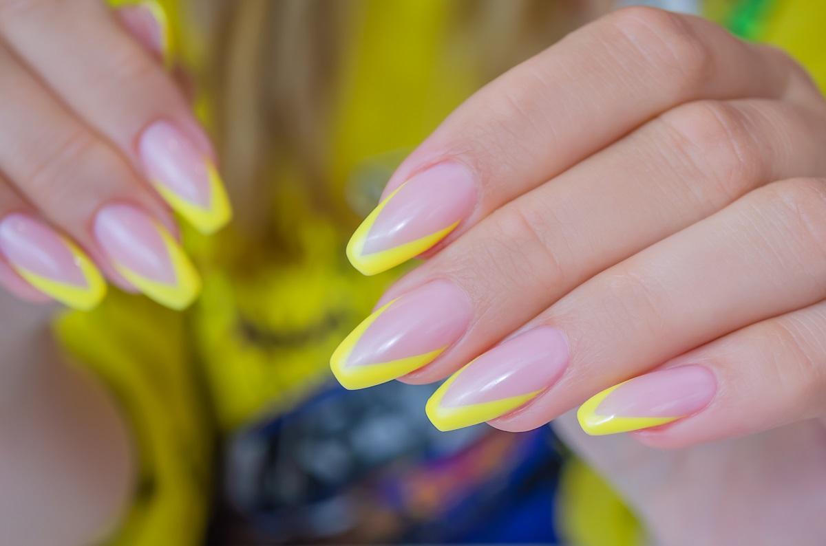o femeie care ține întinse ambele mâini în față pentru a-i putea vedea forma de unghii balerina și culorile de galben pe care le-a ales pentru ojă