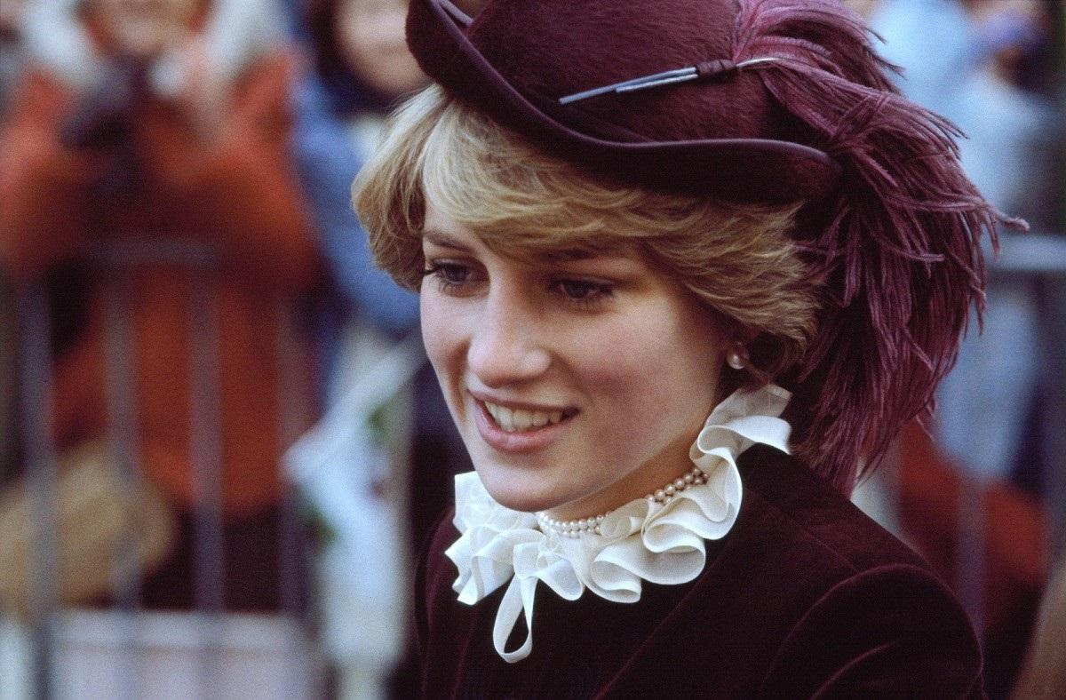 Portret cu Lady Di în timp ce zâmbește oamenilor și poartă o cămasă violet cu guler bufant alb, la care a accesorizat o pălărie mov, într-unul din acele momente emblematice ale Prințesei Diana