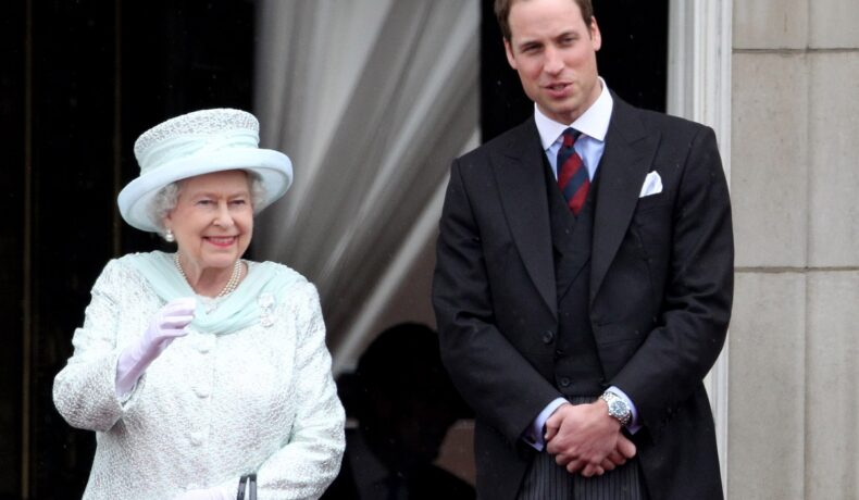 Regina Elisabeta îmbrăcată într-un costum alb cu pălărie de aceeași culoare, alături de nepotul său, Prințul William, în timp ce salută mulțimea de la balcon în cadrul Jubileului de Diamant când PRințul i s-a adresat Majestății Sale cu numele special de alint al Reginei Elisabeta