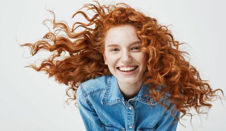 Portretul unei tinere roșcate, zâmbitoare și cu buclele în vânt
