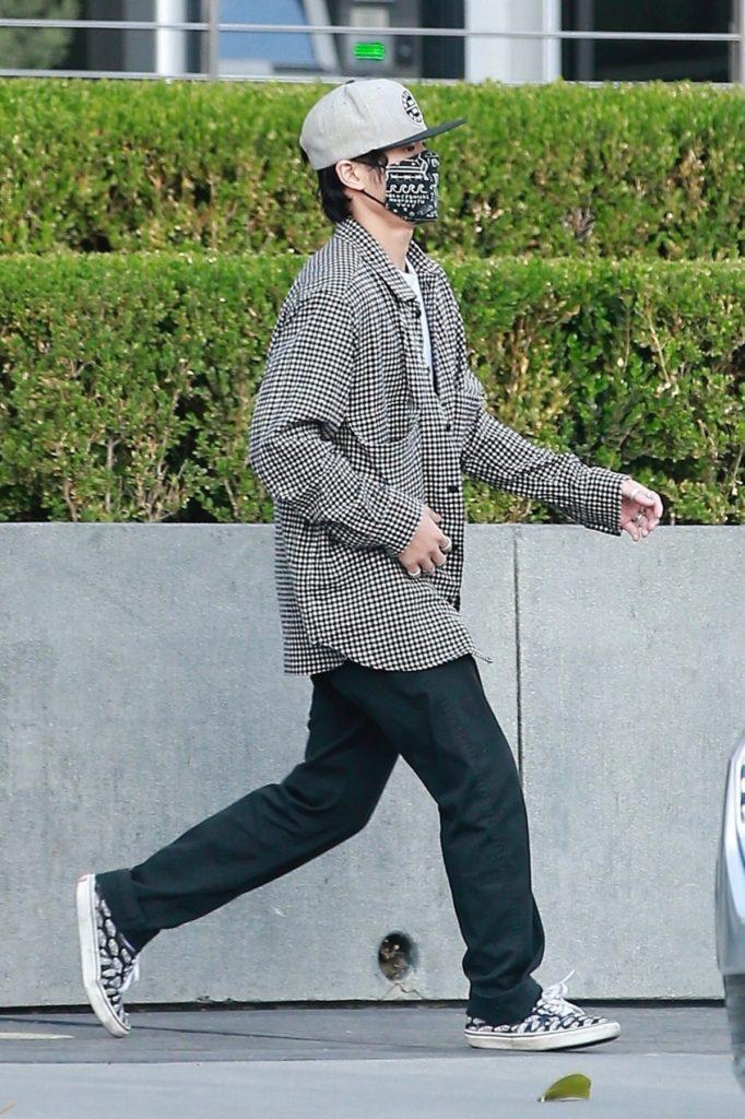Pax Jolie Pitt îmbrăcat în blugi negri și o cămașă gri în carouri în timp ce poartă o șapcă și mască de protecție pe străzile din Los Angeles