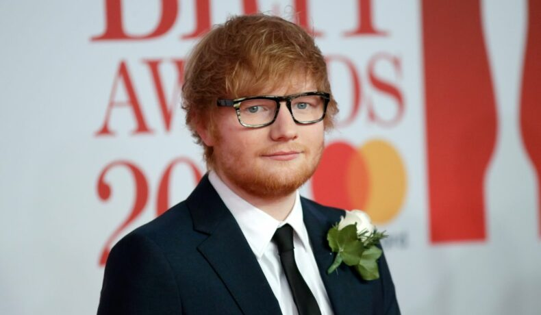 Ed Sheeran poartă un costum negru și o cămașă albă, cu un trandafir alb la rever