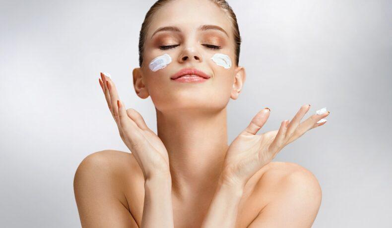 O femeie frumoasă care își aplică pe față două straturi de cremă pe care le folosește ca surse de colagen pentru elasticitatea pielii