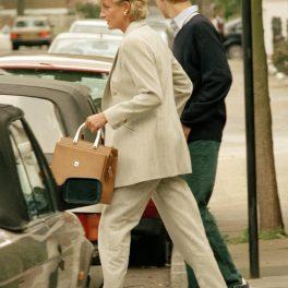 Prințesa Diana într-un costum gri în timp ce ține în mână o poșetă și îl conduce pe fiul său, Prințul William la mașină
