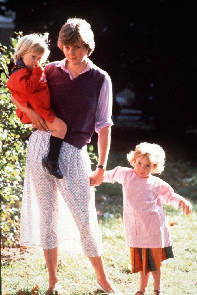 Lady Di într-o fustă cu buline și o vestă mov în timp ce ține o fetiță de mână și a alta în brațe în timp ce lucra la o școală de asistente în 1980, fiind unul dintre acele momente emblematice ale Prințesei Diana
