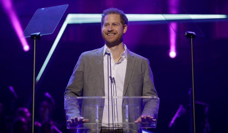 Prințul Harry la costum gri în timp ce stă la pupitru la Premiile Onside, anunță deschiderea Jocurilor Invictus 2022