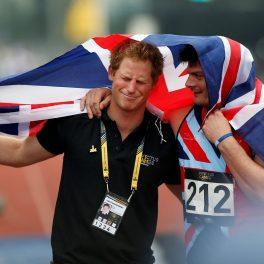 Prințul Harry alături de David Henson în timp ce se țin după umeri și sunt acoperiți cu steagul Marii Britanii pentru a celebra câștigul lui David la Jocurile Invictus din 2014