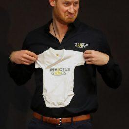 Prințul Harry ținân în mână un body de bebeluș la prezentarea Jocurilor Invictus la Haga în 2019