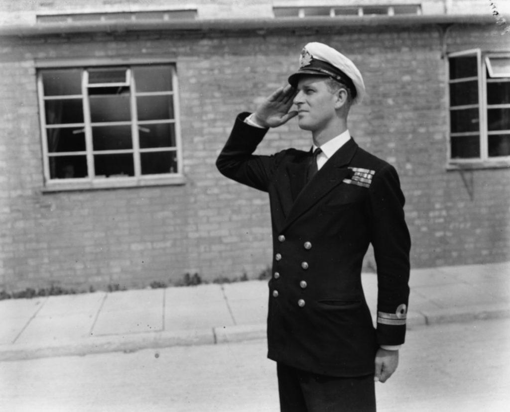 Prințul Philip Mountbatten în timp ce salută Academia Regală Navală în uniformă în anul 1947 înainte de căsătoria cu Regina Elisabeta