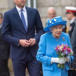 Prințul William îmbrăcat la costum în timp ce stă în spatele bunicii sale, Regina Elisabeta, în timpul unei vizite oficiale din Scoția