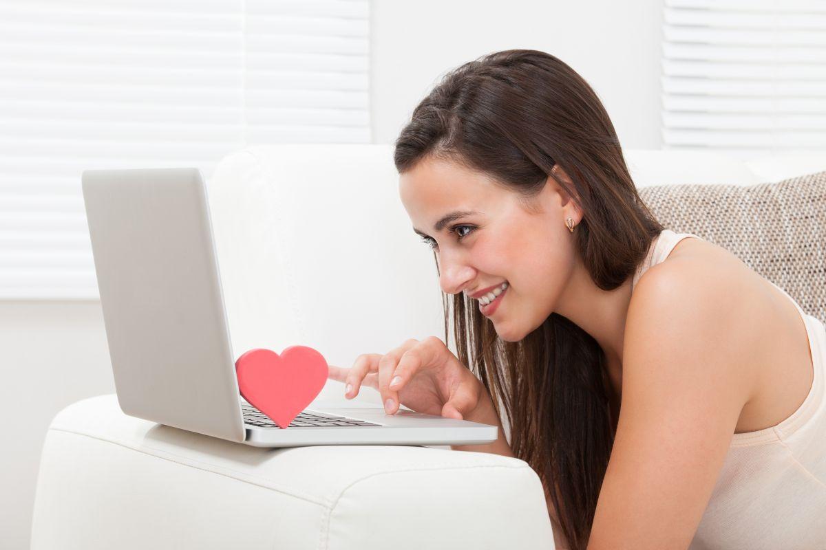 O femeie tânără folosește laptopul, în timp ce zâmbește. Tastatura laptopului are amplasată o inimioară în apropierea ecranului