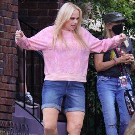 Actrița Rebel Wilson purtând un hanorac roz pudrat și o ăereche de blugi scurți de culoare albastră în timp ce pare să danseze pe platourile de filmare pentru pelicula Senior Year