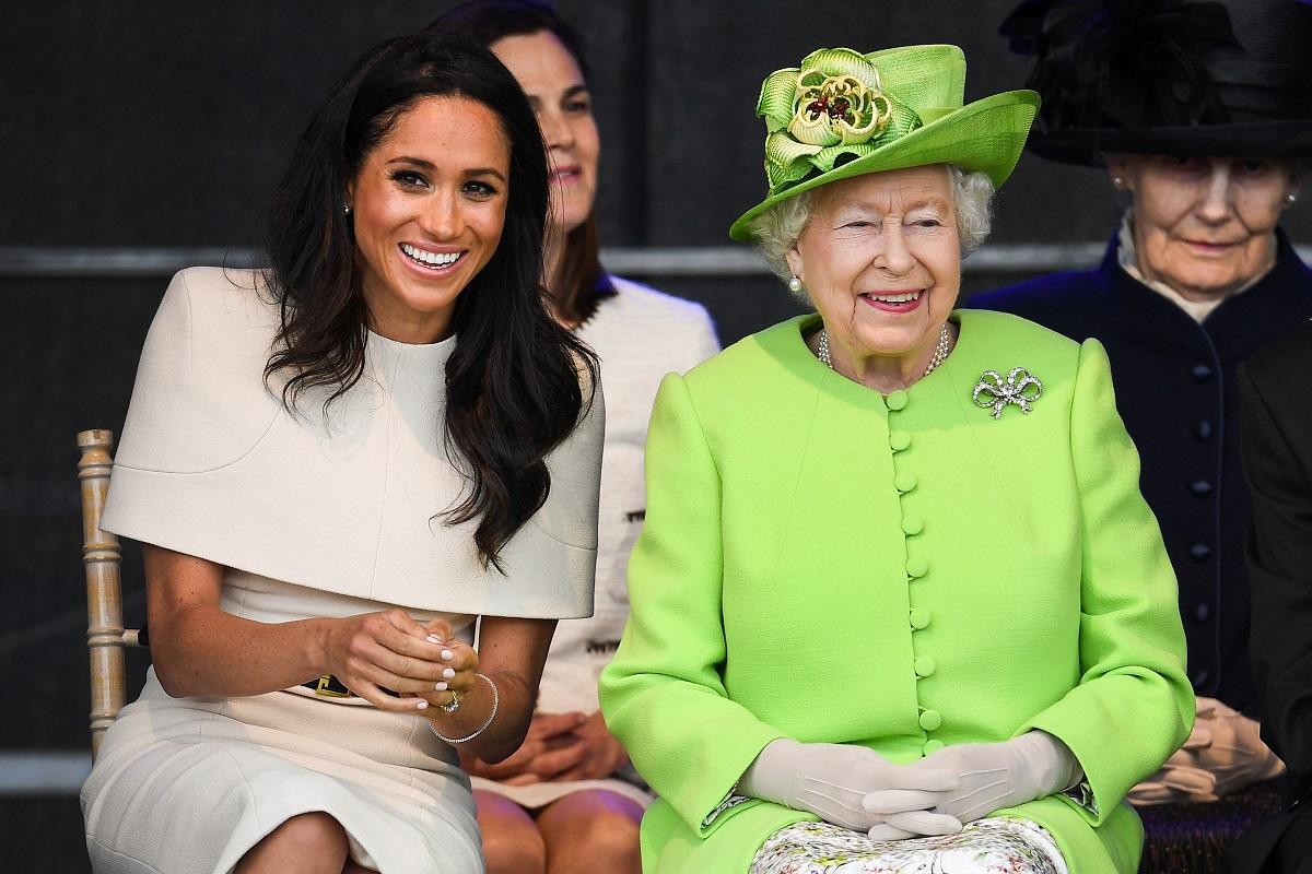 Meghan Markle îmbrăcată într-o rochie albă în timp ce zâmbește alături de Regina Elisabeta care a cunoscut-o pe fiica Ducilor de Sussex printr-o conferință video, în timp ce participă la ceremonia de deschidere a podului de la Widnes în iunie 2018
